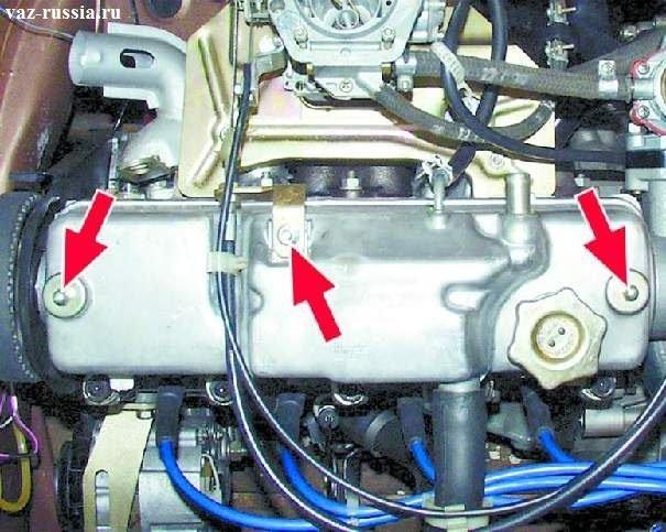 Центральная стрелка указывает на гайку крепления кронштейна привода акселератора. Две боковых стрелки указывают на гайки крепления крышки головки блока