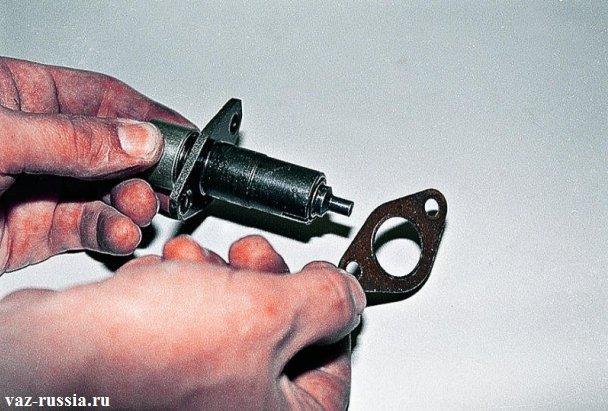 На фото изображена снятая уплотнительная накладка и сам натяжитель цепи