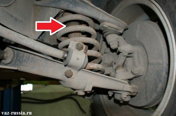 Стрелкой показан передний амортизатор находящийся во внутренней части пружины