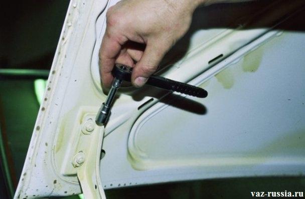 Отворачивание двух гаек крепления крышки, с помощью удлинителя с накидной головкой