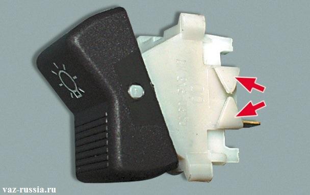 Стрелками показаны пластмассовые защелки, благодаря которым включатель крепится