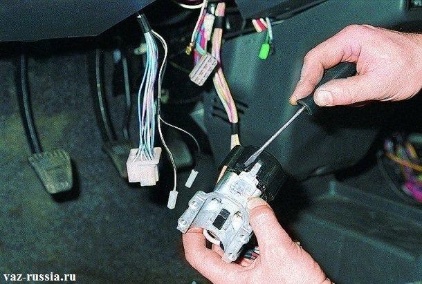 Поддевание отвёрткой пластмассовой защёлки, которая крепит крышку замка