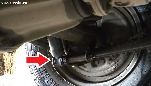 Стрелкой указано место, где болт крепит нижнюю часть заднего амортизатора