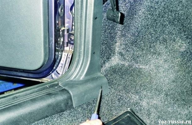 Отворачивание отверткой трех винтов, крепления верхней накладки порогов