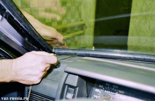 Вытягивание верёвки и слежение за тем, чтобы край уплотнителя перетянулся через ребро проёма