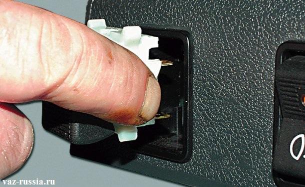 Вставление выключателя в отверстие зажимая при этом его боковые защелки