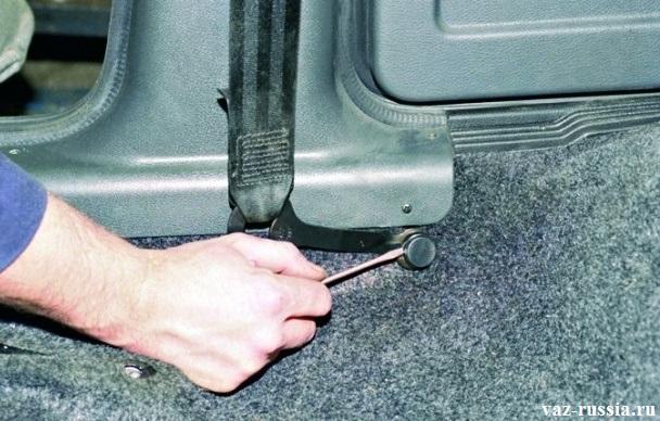 Поддевание отверткой заглушки, которая закрывает болт крепления кронштейна ремня безопасности