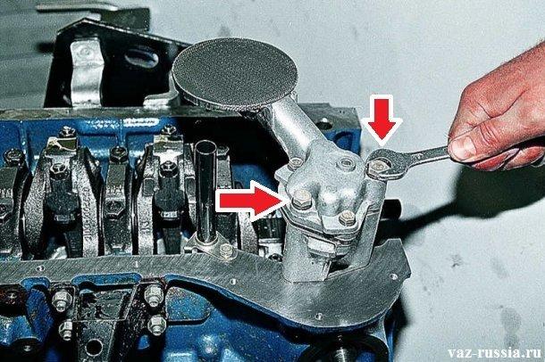 Стрелками указаны болты которые необходимо отвернуть, для того чтобы снять насос с двигателя