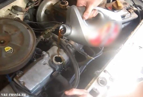 Заливание нового моторного масла через маслоналивную горловину, в двигатель автомобиля