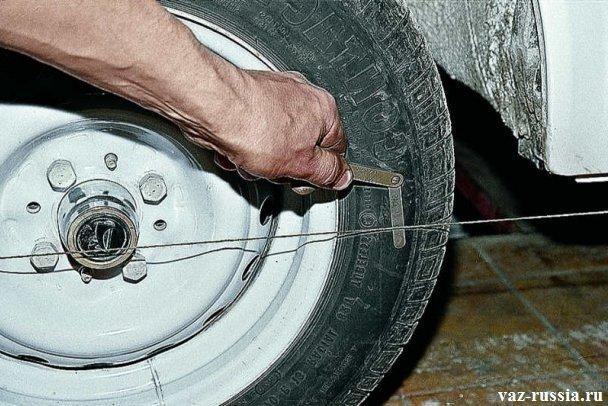 Проверка при помощи щупа того, на сколько касается нитка колеса