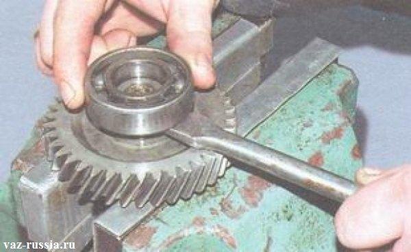 Установленный блок шестерён в тиски и снятие с него подшипника пятой передачи