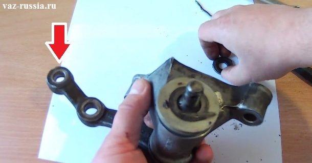 Стрелкой указан кончик маятника, в отверстие которого необходимо вставить крючок идущий от динамометра и после чего узнать с каким усилием крутиться сошка
