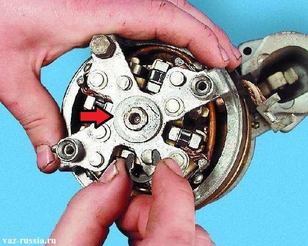 Снятие стопорного кольцо с центральной части электродвигателя, и после чего снятие шайбы которая указана стрелкой