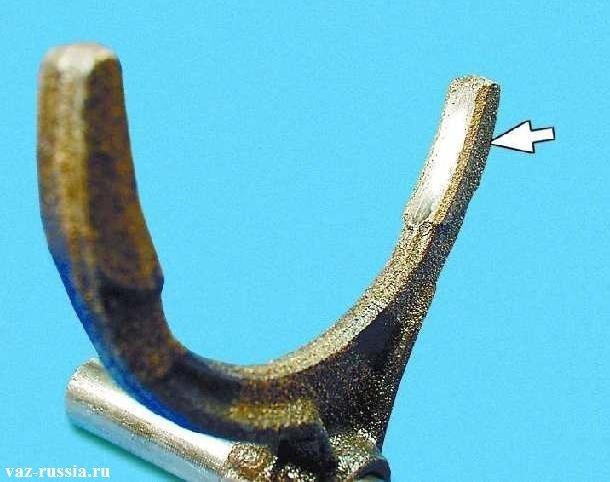 Стрелка указывает на то место где вилка входит в контакт с кольцевым пазом синхронизатора