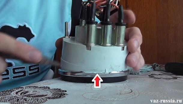 Стрелкой указано место с которого необходимо начинать поддевать окантовку