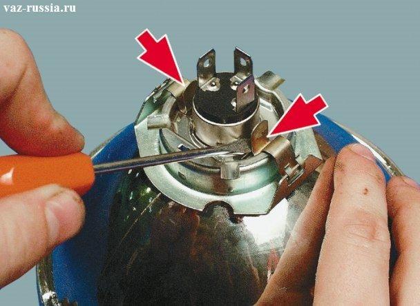 Отгибание защёлок которые крепят лампочку в наружной фаре