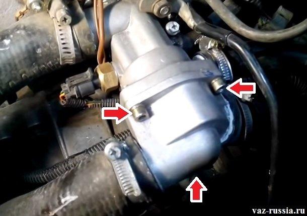 Стрелками указаны три болта которые крепят крышку термостата
