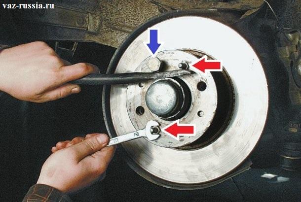 Удерживание монтажной лопаткой самого диска от проворачивания, и отворачивание в этом момент направляющих штифтов которые указаны красной стрелкой