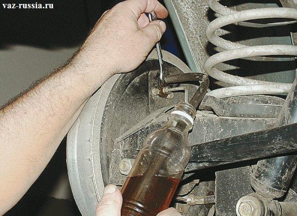 Ослабление штуцера заднего колеса и тем самым выливание отработанной тормозной жидкости в бутылку
