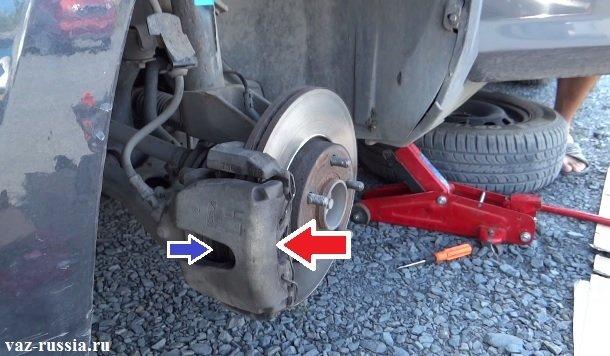 Красной стрелкой показан сам суппорт, а синей стрелкой указано отверстие через которое можно взглянуть на сами колодки