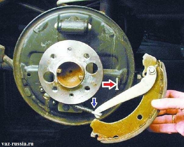 Снятие задней колодки и отсоединение рычага от удерживающей планки которая указана синей стрелкой
