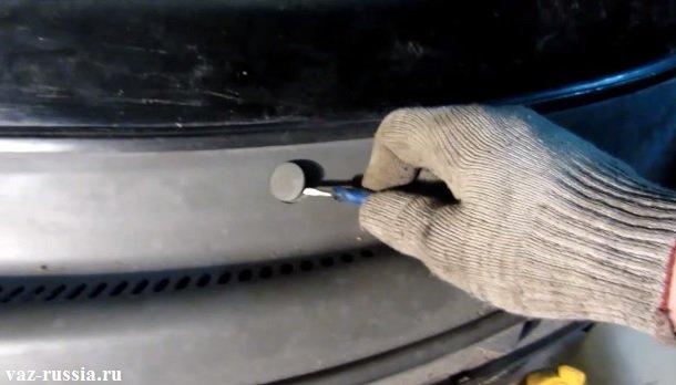 Поддевание заглушки, под которой располагается винт крепления верхней части ветровой накладки