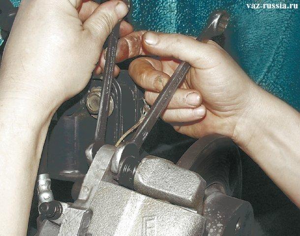 Удерживание направляющего пальца от проворачивания и отворачивание болта крепления скобы тормозного суппорта