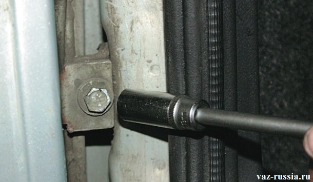 Отворачивание с помощи накидной головки верхнего и нижнего болта крепления петлей к кузову