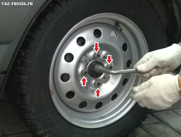 Четыре болта крепления колеса к автомобилю показаны стрелками