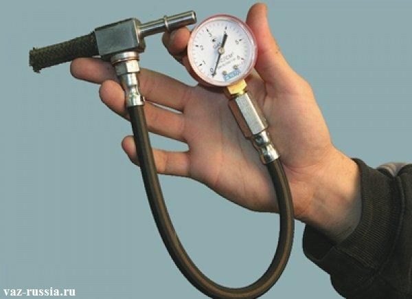 На фотографии человек держит в руках манометр которой идёт специально для проверки давления в системе питания