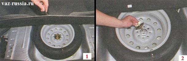 Вынимание запасного колеса из багажного отделения