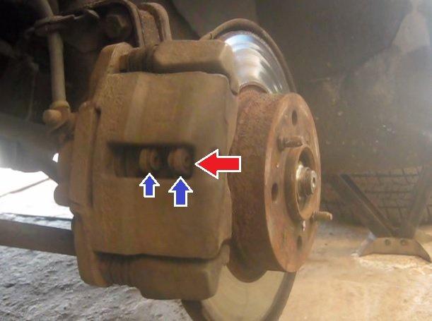 Красной стрелкой указано отверстие в скобе тормозного суппорта, а двумя синими тормозные колодки