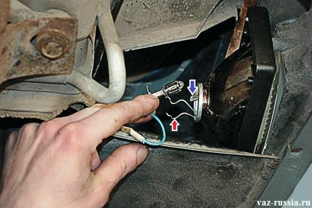 Снятие пружинного фиксатора который указан красной стрелкой с крючка который располагается на самой фаре и извлечение лампочки из отверстия в котором она находиться