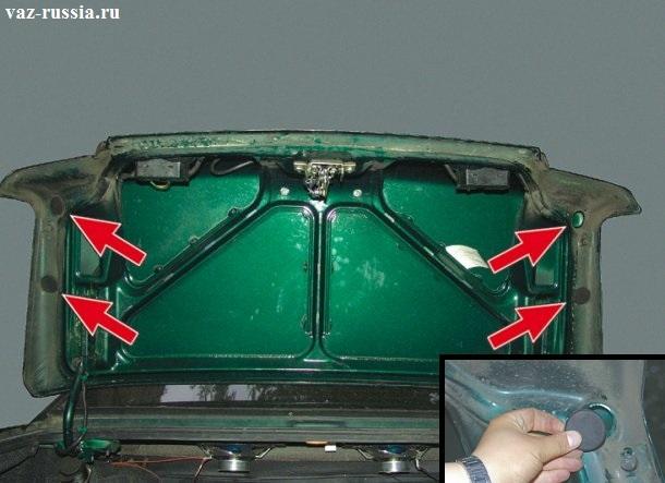 Четыре резиновые заглушки за которыми находятся гайки и болты крепления спойлера