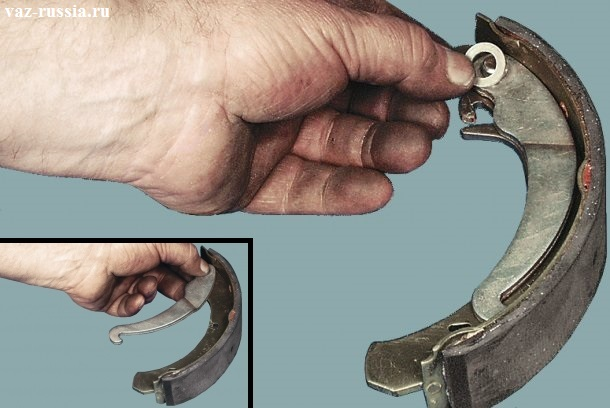 Вынимание шплинта, снятие после этого стопорящей шайбы и нажатие на палец крепящий рычаг, снятие его с колодки