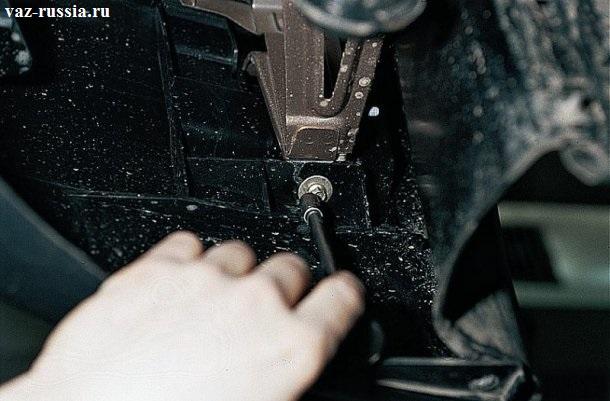 Отворачивание нижнего болта крепящего в боковой части передней бампер, чтобы увидеть данный болт вам нужно будет заглянуть под нижнюю часть бампера так как он находиться внутри него