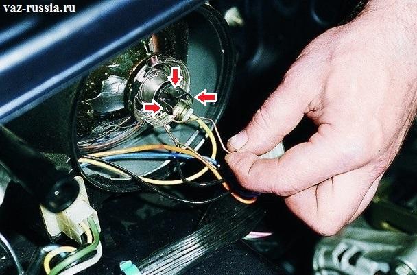 Стрелками указаны выводы за которые необходимо вытаскивать лампочку, а на фото происходит отсоединение проволочной защёлки которая удерживает лампу на одном месте