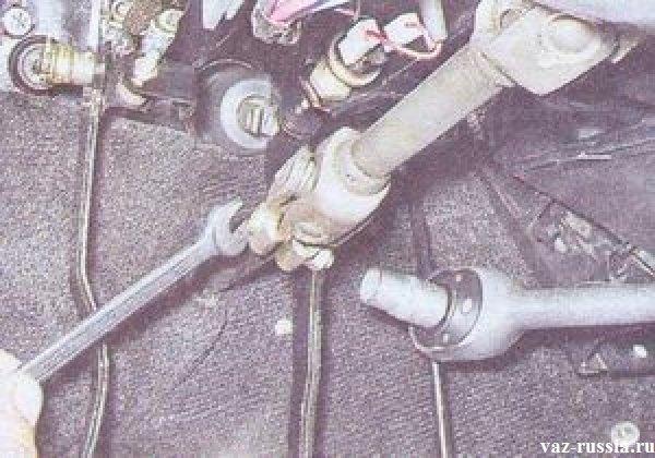 Выворачивание гайки болта, который скрепляет карданный шарнир с рулевым валом который идёт от редуктора