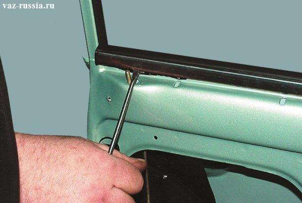 Поддевание отвёрткой внутренней хромированной окантовки двери и её снятие