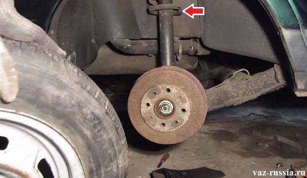 Стрелкой показано где пружина на амортизаторной стойке располагается