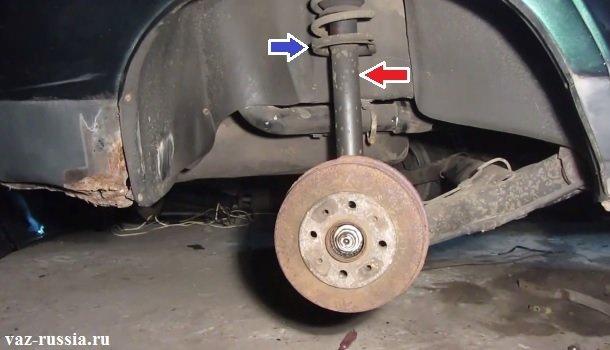Местоположение стойки показано на фото а стрелками указаны амортизатор и её пружина