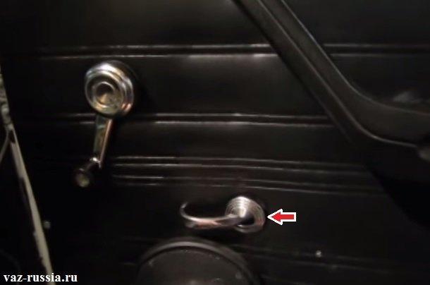 Стрелкой указано место в котором облицовку ручки открывания достаточно поддеть и после чего её можно будет снять с машины