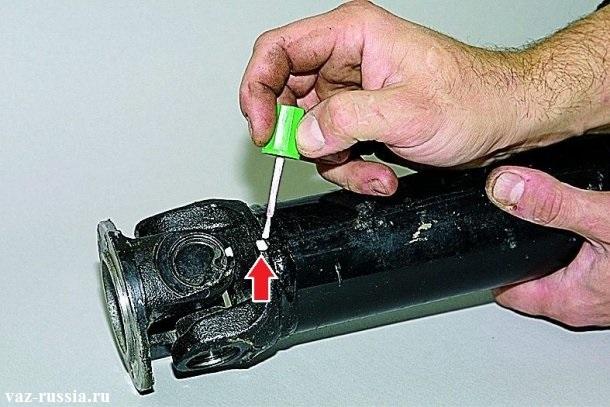 Нанесение при помощи корректора меток, а именно метки на корпусе карданного вала, относительно вилки, это нужно для того чтобы потом всё обратно точно так же собрать