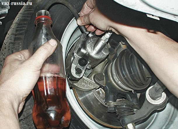 Одевание кончика шланга на штуцер для прокачки и опускание второго конца шланга, в бутылку