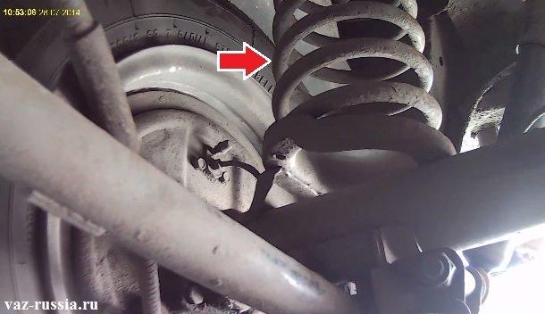 На фотографии стрелкой указано местонахождение задней пружины