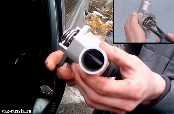 Извлечение при помощи пассатижей термоэлемента из крышки термостата