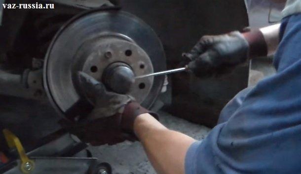 Поддевание защитного колпачка плоской отвёрткой и его снятие